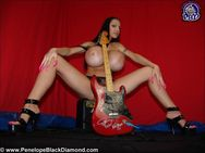 Busty rocker Penelope Black Diamond posing with her Guitar