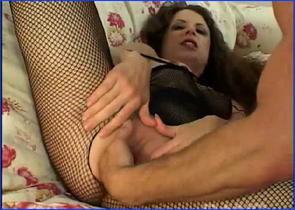 Lena Ramon is a small boobed brunette, who's wearing a crotchless, fishnet, body suit, while laying b